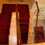 RED TRADITOINAL STAIR RUNNER INSTALLED CONTINUOUSLY ON STAIRS WITH COORDINATING ENTRY WAY RUG OVERLAND PARK KS